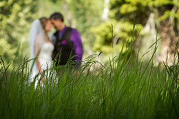 Wedding couple kissing behind the foreground of grass