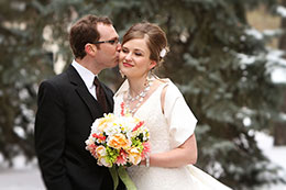 A wedding kiss on the cheek in the snow in Edmonton