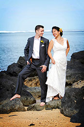 Bride and Groom pose barefoot on black rocks of Hawaii
