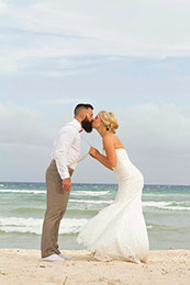Bride pulls Groom in for a kiss by his suspenders in Playa del Carmen