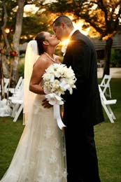 The sun shines through a passionate wedding kiss