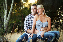Lovely couple sits for a photo in a vineyard