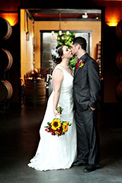 Bride and Groom kiss in the barrel room of JM Cellars