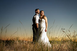 Bride and Groom stand in a field during sunset