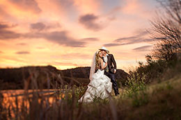 Wedding couple kisses on the banks of Rio Grande under a blazing sunset
