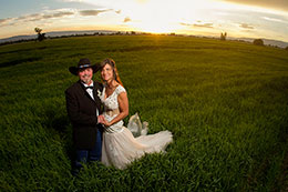 Newly married couple stands in field at sunset