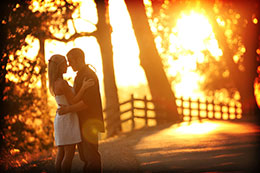 Engaged couple along a roadside with firery sunset