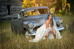 Beautiful Bride sits on an old junkyard car