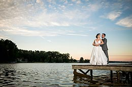 Keith and Erica stand on a dock at Lake Oconee during sunset