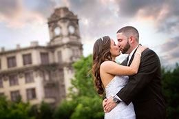 Kissing under a dramatic sky with the clock tower in the background