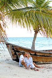 Couple snuggles beside an old boat and a palm tree