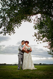 Bride and Groom embrase under a tree at 7N Ranch at sundown