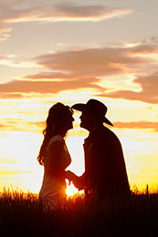Radient sunset silhouettes bride and cowboy groom