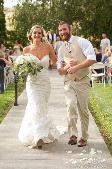 Bride and Groom skip down the isle at Shadow Lake Ranch