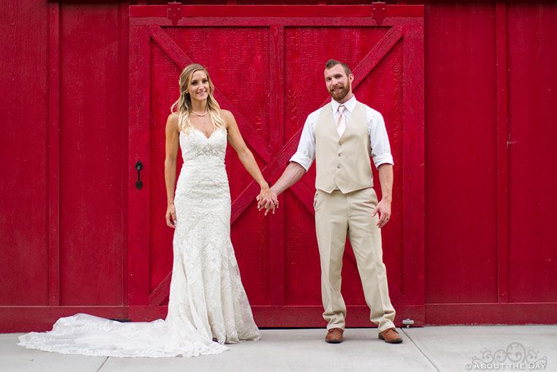 Bride and Groom in front of red barn door at Shadow Lake Ranch