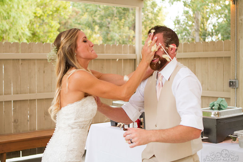 Bride shoves cake in Grooms face at Shadow Lake Ranch