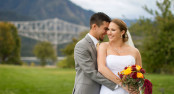 Bride and Groom cuddle with Bridge of the Gods in background on Thunder Island