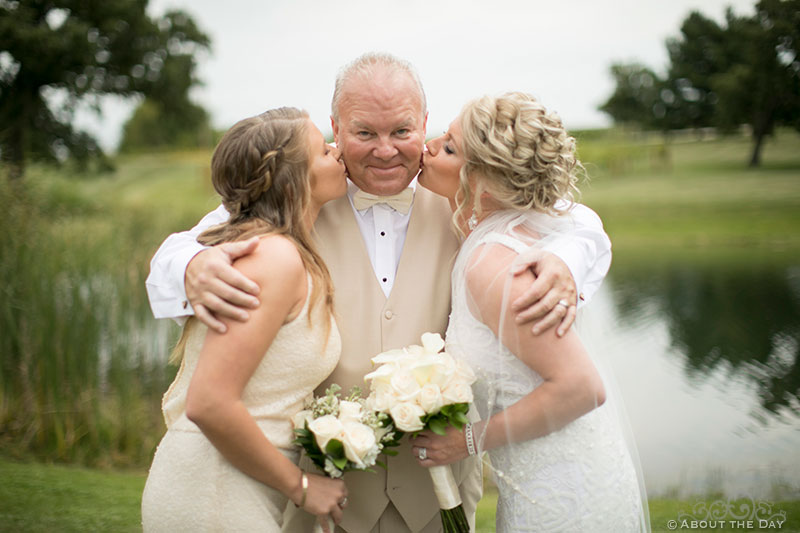 The bride and her sister kiss a proud dad on the cheeks