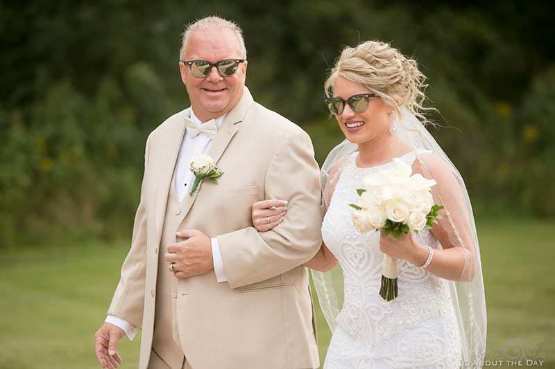 Bride and her dad walk down the isle with sunglasses