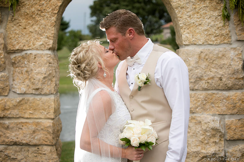 Bride and Groom kiss in stone archway at DC Estate Winery
