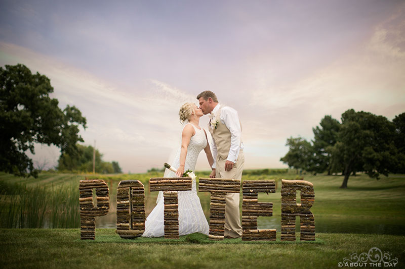Brent and Heather kiss behind a sign of their last name under a dramatic sky