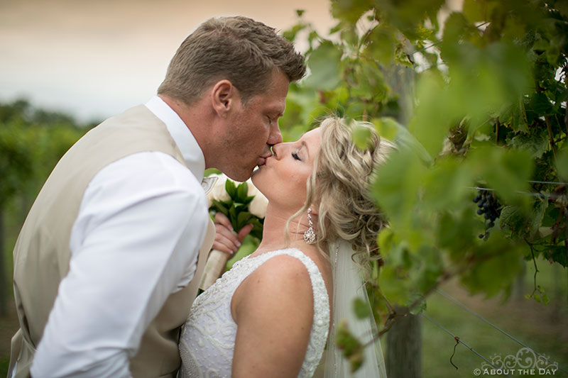 Bride and Groom kiss in the rows of grapes
