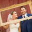 Bride and Groom hold their own frame for picture Wedding decor at Youngs Dairy Farm Barn in Auburndale, WI