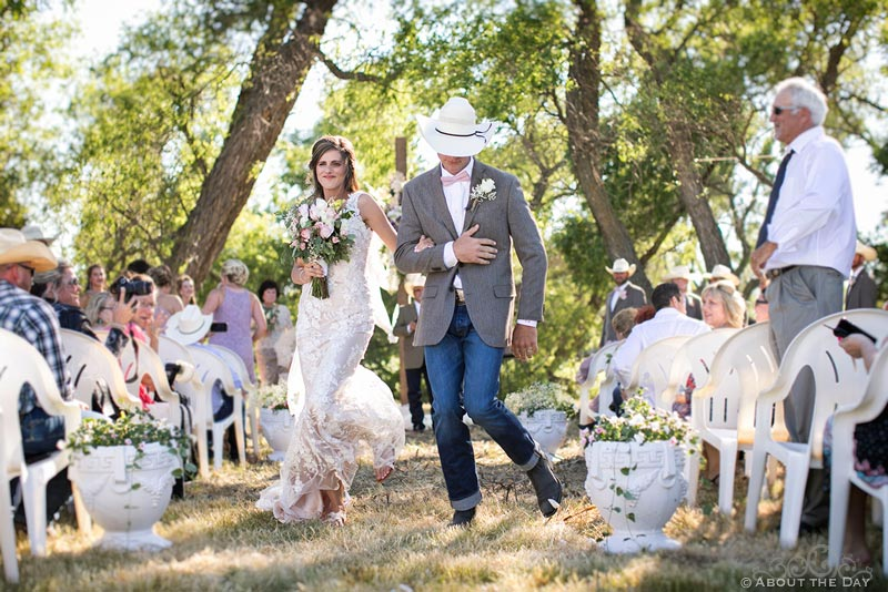 Bride and Groom dance down the isle at country wedding ceremony