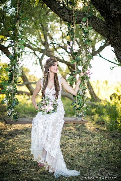 Beautiful Bride sits in a rope swing with flowers at Haythorn Land & Cattle Co