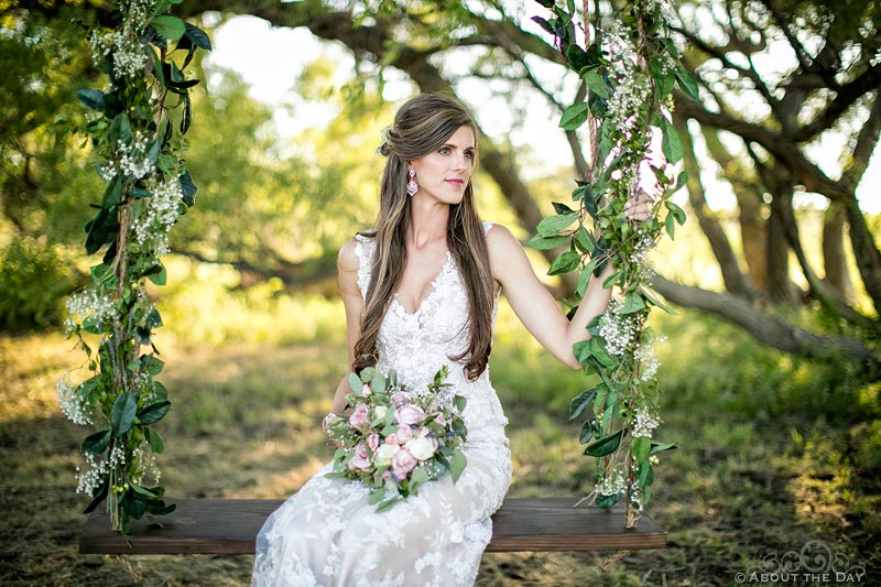Stunningly beautiful Bride sits in a rope swing with flowers at Haythorn Land & Cattle Co
