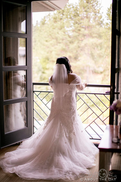 Bride poses out a open window at the Harbor Club in Bellevue Washington