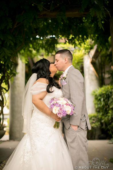 Bride and Groom kiss under the arbor at the Harbor Club in Bellevue Washington