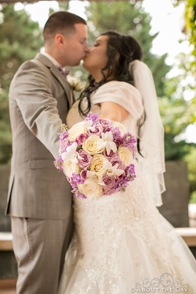 Bride and Groom kiss while holding out flowers