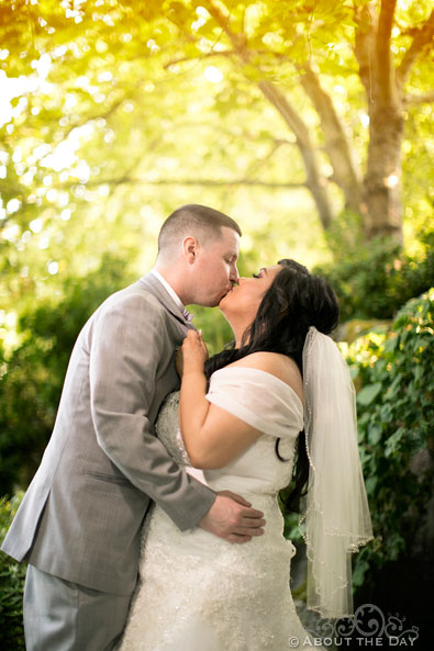 Bride and Groom kiss in the woods at the Harbor Club in Bellevue Washington