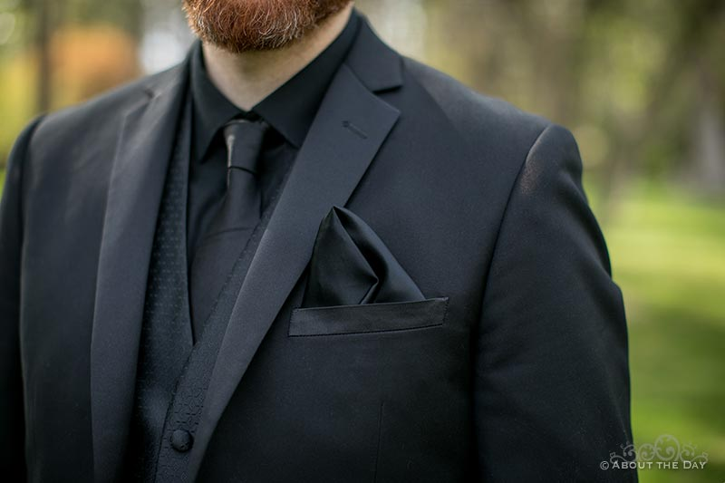 Close up detail of David's all black tux