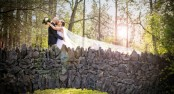 Bride and Groom kissing on stone bridge