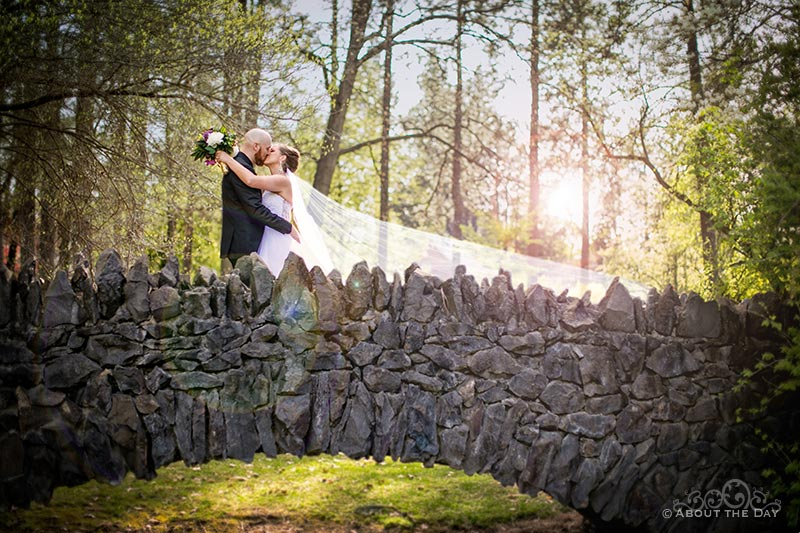 Bride and Groom kiss on stone bridge