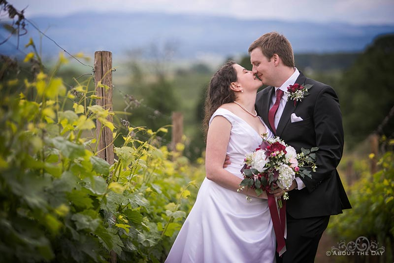Steven and Lauren kiss in the Legacy Estate Vineyard