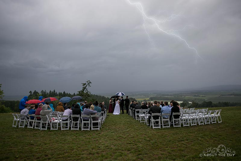 Bride & Groom with lightning during their ceremony at the Legacy Estate Vineyard
