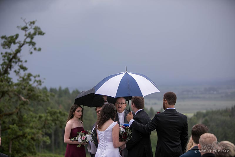 Vows in rain soaked wedding ceremony at the Legacy Estate Vineyard