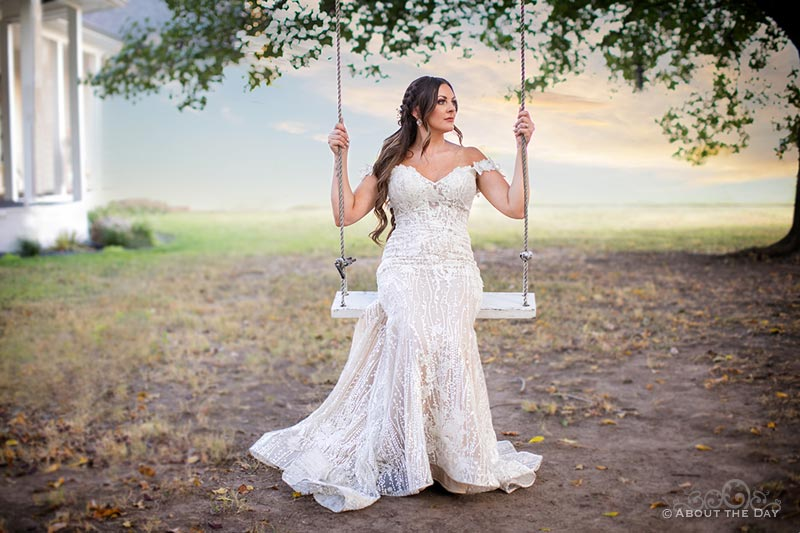 Bride sits in the rope swing at The Emerson
